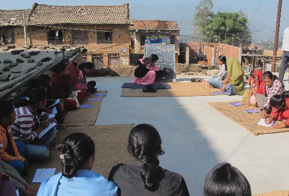 Theoretischer Unterricht über die Herstellung von Lapsi-Trockenfrüchten in einem Nachbardorf. Wie traditionell üblich, sitzen die Frauen auf Matten auf dem Boden.