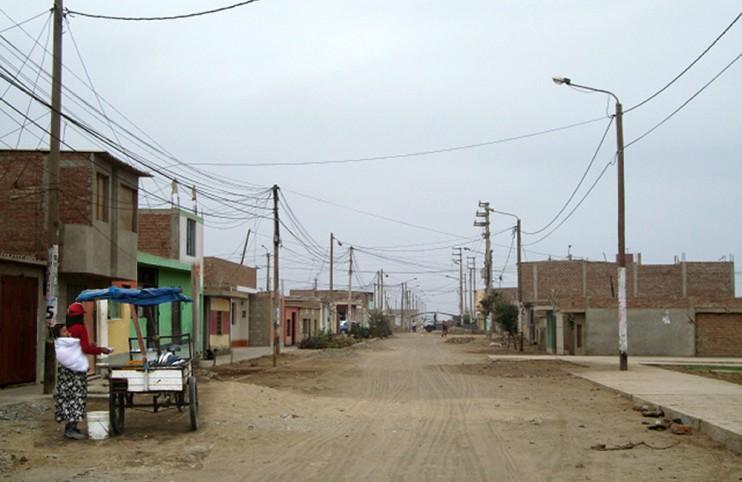 Straße im ersten Armenviertel der Aktivitäten in der Großstadt Trujillo. Im Vordergrund eine Frau, die mit ihrem Kind auf dem Rücken auf Kundschaft für Imbisse aus ihrer kleinen Garküche hofft. (Foto: NRO Micaela Bastidas)
