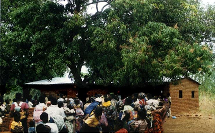 Frauen aus Chamba und Umgebung warten mit ihren Kindern auf den monatlichen mobilen Gesundheitsdienst. Im Hintergrund der Rohbau der Gesundheitsstation. (Foto: Dr. Gabriele Gahn)